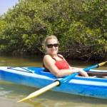 Photo d'une jeune femme appréciant tranquillement l'activité de kayak sur la Semois
