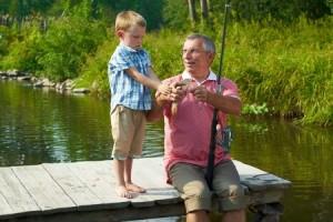 Jeune enfant pratiquant la pêche avec son grand-père